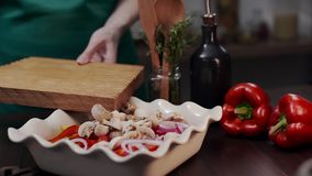 The cook makes meal with champignons and vegetables, chef adds champignons to the meal, vegetarian and gealthy recipe to stock video footage