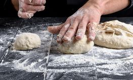 Cook making dough balls on a black wooden table. Close up stock image