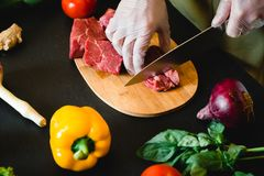 Cook man cutting meat on a board. Raw vegetables on a dark table. Top view. Food concept. Cook man cutting meat on a board. Raw vegetables on a dark table. Top Royalty Free Stock Photos
