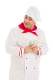 Cook man holding fan of dollars wearing white uniform Royalty Free Stock Photography