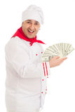 Cook man holding fan of dollars wearing white uniform. In the studio over white background. isolated Royalty Free Stock Photos