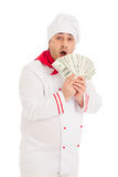 Cook man holding fan of dollars wearing white uniform. In the studio over white background. isolated Royalty Free Stock Images