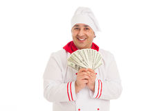 Cook man holding fan of dollars wearing white uniform. In the studio over white background. isolated Royalty Free Stock Image