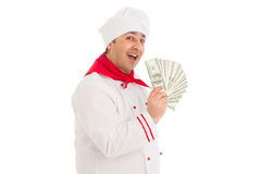 Cook man holding fan of dollars wearing white uniform. In the studio over white background. isolated Stock Photo