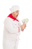 Cook man holding fan of dollars wearing white uniform. In the studio over white background. isolated Stock Photography
