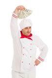 Cook man holding fan of dollars wearing white uniform. In the studio over white background. isolated Royalty Free Stock Photography