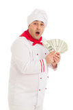 Cook man holding fan of dollars wearing white uniform. In the studio over white background. isolated Stock Photos