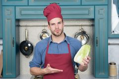 Cook man point hand at chinese cabbage. Chef in red hat, apron with vegetable in kitchen. Vegetarian, health, diet, vitamin. Food, cooking, cuisine, menu Stock Photography