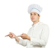 Cook man points hand over white. Young smiling cook man points hand over white Royalty Free Stock Images