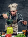 A cook man preparing vegetable cocktail in a blender. A cook man holds tablet PC and thinking how to prepare the fresh vegetable cocktail in a blender royalty free stock photography
