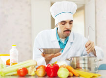 Cook man  tasting soup  from pan Stock Photography