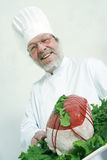 Cook and meat. Senior cook holding a raw roastbeef on a tray Stock Photography