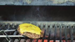 Cook melts cheese on a Cheeseburger. Cook uses a blow torch to melt cheese on a meat cutlet. Cook melts cheese on a Cheeseburger. Cook uses a blow torch to melt stock photography