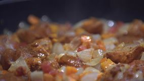 Chopped onions, carrot and tomato fried in vegetable oil in the pan. Close-up adding chicken on top of the pan. stock footage