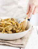 Cook mixing pesto with penne rigate pasta Stock Image
