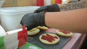Cook nalewa majonez na babeczkach dla hamburgerów zbiory wideo