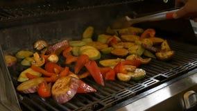 Cook obraca z pomocą forceps różnorodni warzywa tak jak oberżyna, pieprz, zucchini i pieczarki, zdrowa żywność zdjęcie wideo