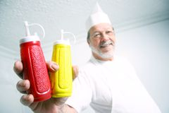 Cook offering condiments Royalty Free Stock Image