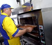 Cook by the oven. A cook inserts a dish in the oven royalty free stock images
