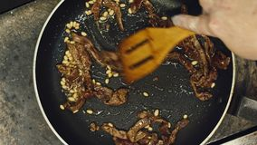 The cook pan fries meat. The man fries meat on the burning frying pan. Fire on a frying pan. Close up. Roasting of meat. Fire on a frying pan stock video