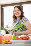 Cook - Plus size happy woman holding cookbook. In kitchen Stock Images