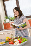 Cook - Plus size happy woman holding cookbook Royalty Free Stock Photography