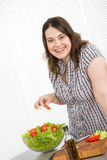 Cook - Plus size happy woman preparing salad Stock Images