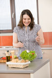 Cook - Plus size happy woman preparing salad Stock Photo