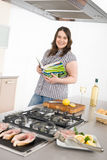 Cook - plus size woman grill fish in kitchen. With white wine and cookbook Stock Image