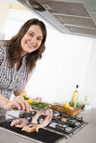 Cook - plus size woman grill fish in kitchen. With white wine and cookbook Stock Photos