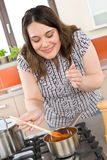 Cook - plus size woman tasting tomato sauce Stock Image