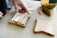 Cook in polyethylene gloves making a sandwich on a white board royalty free stock photo