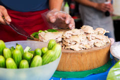 Cook with poultry and cucumbers at street market Stock Images