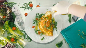 The cook pour the oil on omelet. A white plate with omelet, greens and tomatoes in close-up. Cook take the bottle with oil and pours the omelet. The cook