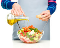 Cook is pouring olive oil into salad Stock Photo