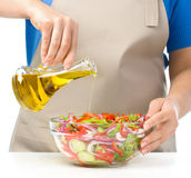 Cook is pouring olive oil into salad Stock Image