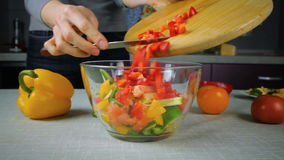 Cook pours in a bowl salad ingredients. The girl cook pours in a bowl salad ingredients. Salad with cucumbers, tomatoes, arugula, peppers stock video