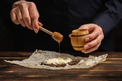 The cook pours honey on bread.  stock photography