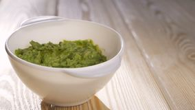 The cook pours olive oil into a bowl of guacamole. Healthy food concept, mexican national dish.  stock video