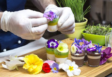 Cook prepares canapes. Dessert edible flowers and buds Stock Photo
