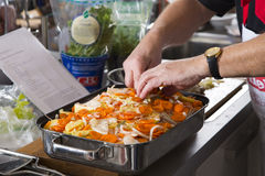 Cook prepares a casserole. A cook prepares a casserole with potatos and carrots Stock Image