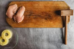 Cook prepares chicken on a wooden cutting board, chicken, pineapple, meat tenderizer. recipe for chicken fillet with cheese and stock photos