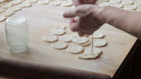 Cook prepares dumplings. Woman preparing vareniki (dumplings, pierogi) on wooden board for boiling. Cook prepare traditional Ukrainian cuisine. Mother is making stock footage
