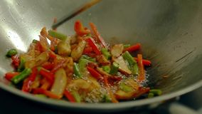 Cook prepares fresh vegetables in a frying pan in boiling oil. Stir with a wooden spatula.