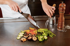 Cook prepares fried vegetable dish Stock Photo