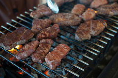 The cook prepares juicy steaks from marbled veal on grill Stock Image