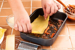 Cook prepares meat lasagna Royalty Free Stock Photography