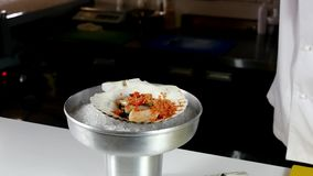 The cook prepares a sea salad of scallops. The chef prepares a sea salad of scallops with various spices in the restaurant`s kitchen. Slow motion shot. Recipes stock video footage