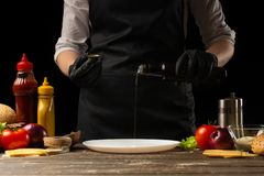 The cook prepares the surface by pouring butter for beef patties, with ingredients on the background, restaurant business, fast stock photos