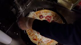 Cook preparing a crepe with cheese, Turkish sauge (sucuk) and egg. Top view of a cook preparing a crepe with cheese, Turkish sauge (sucuk) and egg stock video footage